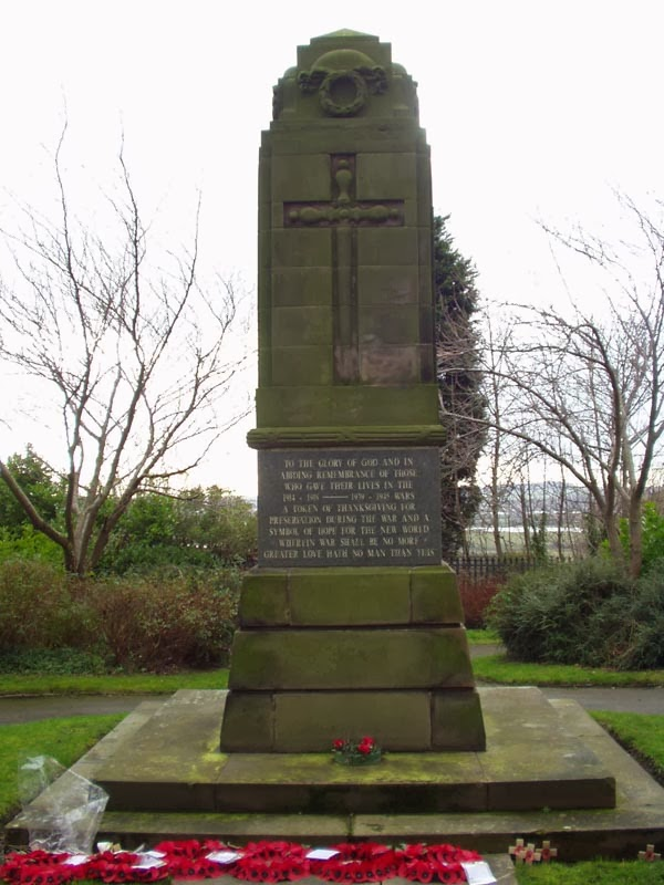 A tall monolythic memorial.  It has a steped top with a carved wreath above a cross of sacrifice.  A granite plaque bears an inscription.  In this picture there are several poppy wreaths lying on the ground in front of the memorial