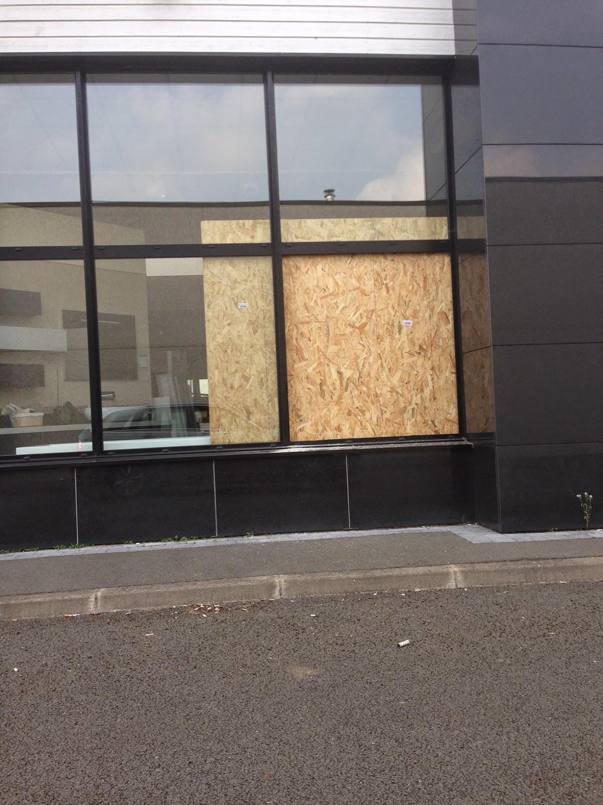 Fermeture provisoire d'une baie vitrée vandalisée sur Lille avant son remplacement.