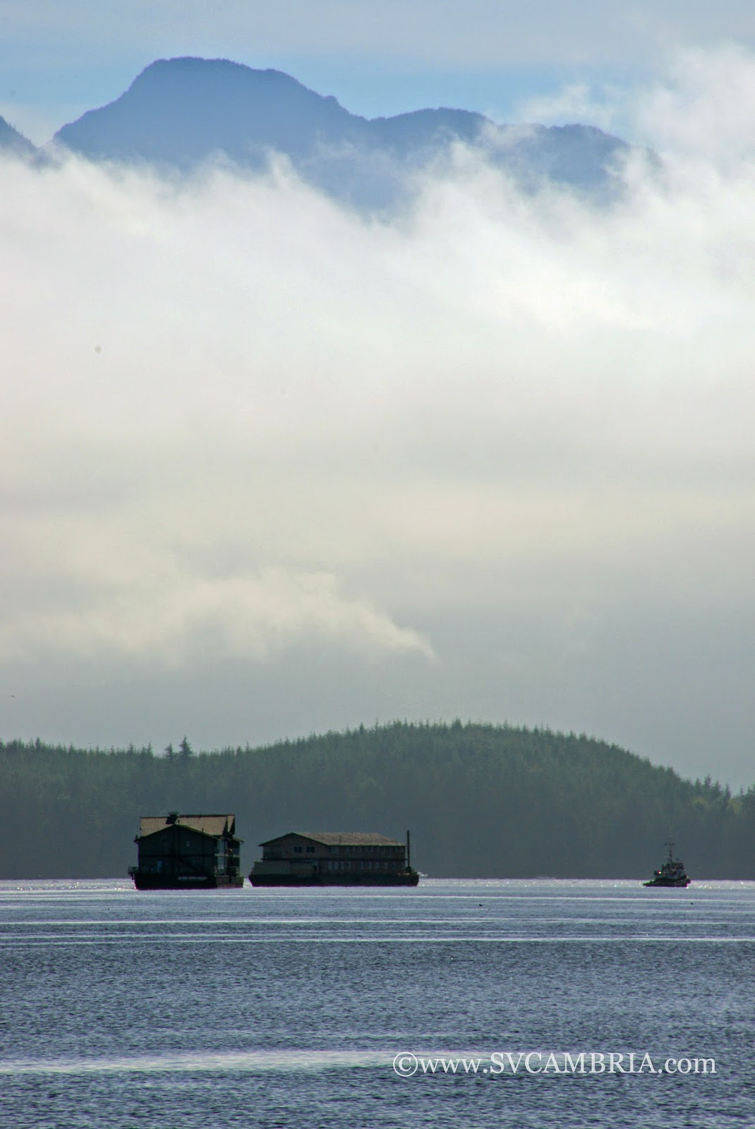 A tug towing two apartment buildings or lodges down Johnstone Strait.