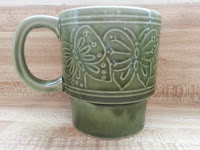 green mug with a butterfly design