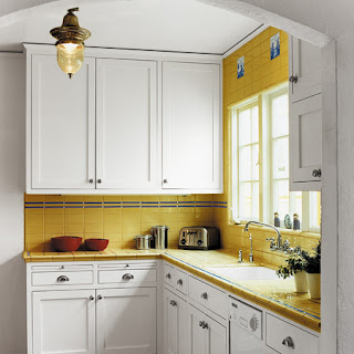 small classic kitchen with yellow tiles and white wooden cabinets