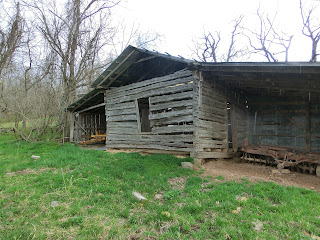 One room cabin with livestock shelter attached to the sides.