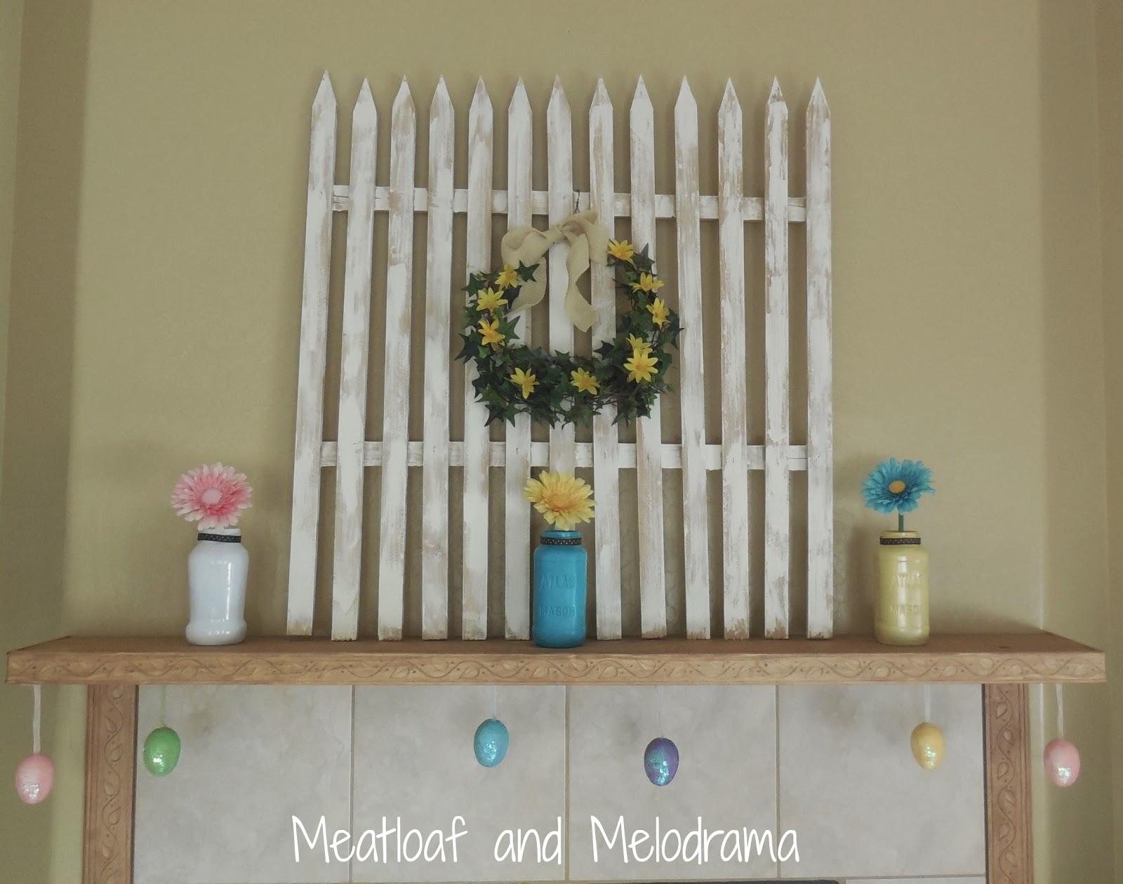 picket fence, flowers and Easter eggs on spring mantel