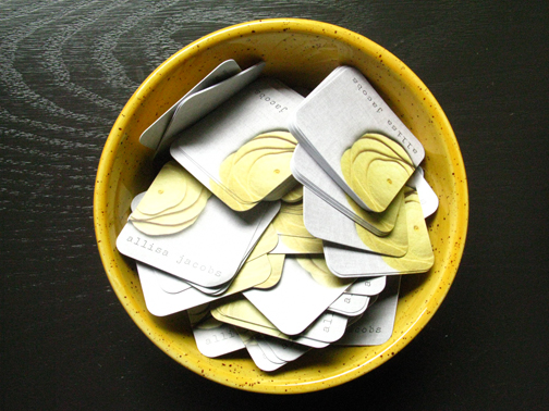 round-cornered, square business cards in yellow bowl on table