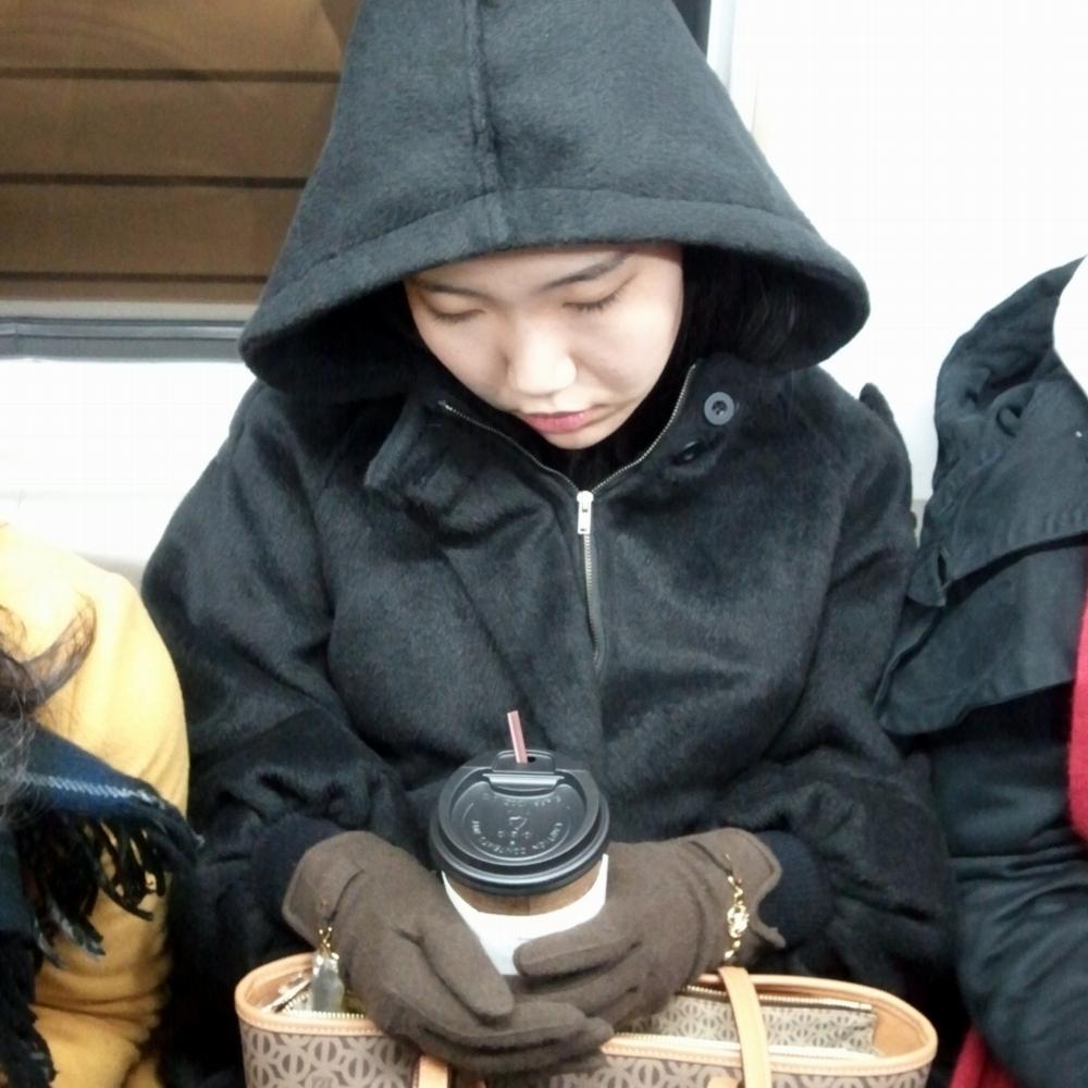 Chica coreana durmiendo en el metro con un café