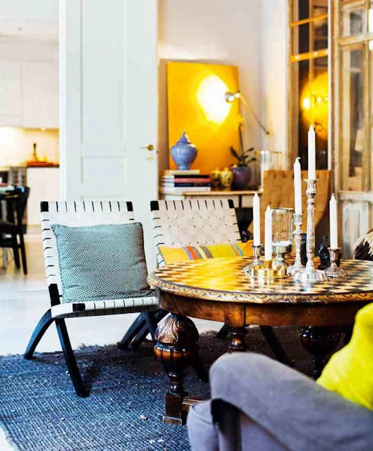 Aranżacja salonu z żółtymi akcentami w postaci poduszek i obrazu