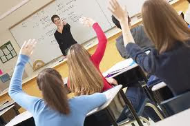 teacher in front of class room with kids raising their hands