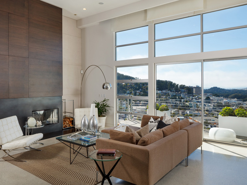 Living Room With Fireplace And Large Windows Overlooking The City