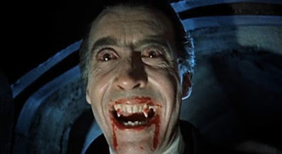 Actor Christopher Lee grins evilly, showing bloody fangs as Dracula.