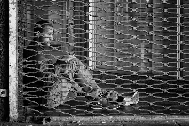 A man sits behind security bars outside the Cape Town bus terminus