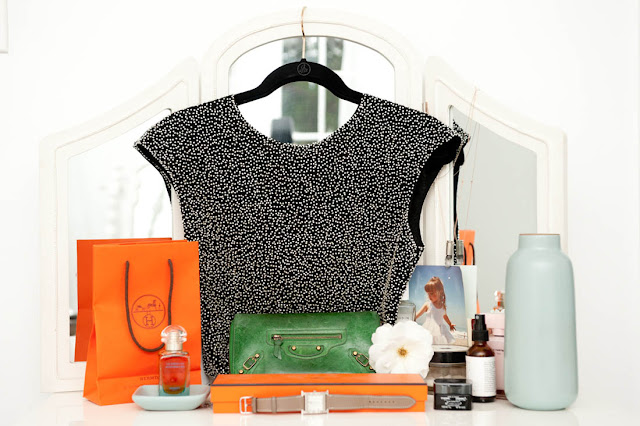 Vintage beaded top hanging on a dressing table mirror with Hermes shopping bag and box, a green clutch purse, some beauty products and perfume and a photo of a little girl as accents