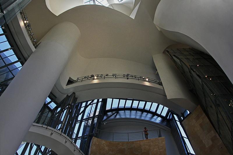 Vista de baixo, do interior do museu sobre dois patamares de dois pisos, tendo um deles uma pessoa a olhar para baixo
