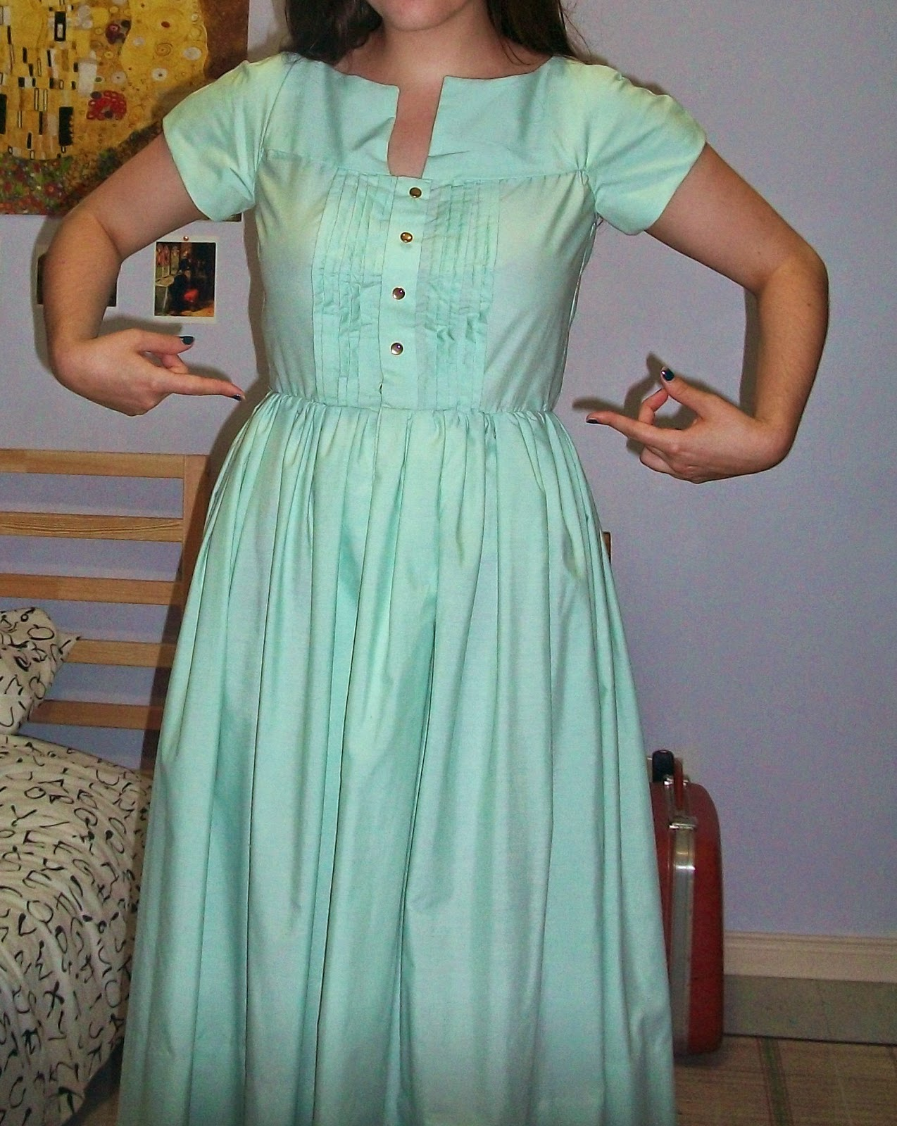 Photo of woman in green dress pointing at her waist.