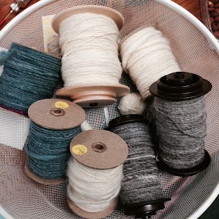 This is a photograph of bobbins with colorful, awesome yarn.