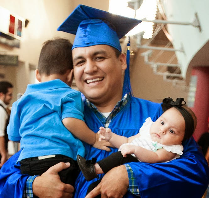 photo of a 2014 grad in cap and gown, smiling, holding his children.