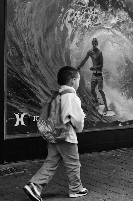 A boy walks past a poster of a surfer