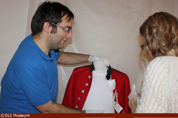 Mounting a tunic on a mannequin to be photographed at the DLI Museum