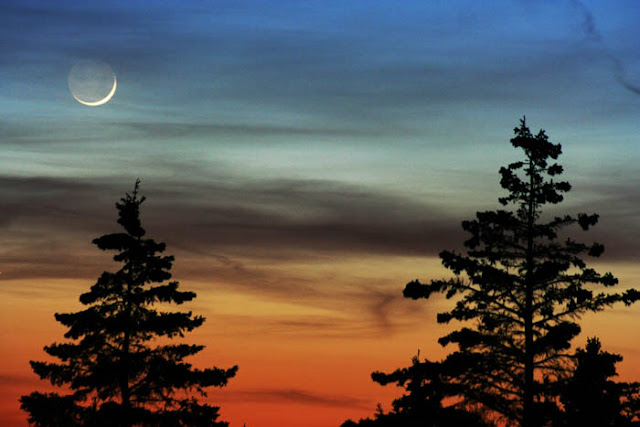 A colorful sunset and a crescent moon while summer camping in Wisconsin.