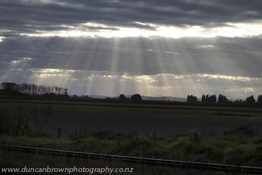 Late afternoon sun streaming through the clouds, seen from Clive photograph