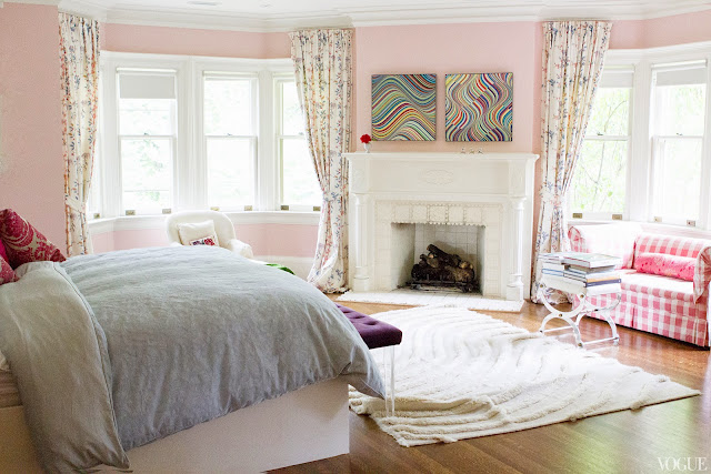 Pink master bedroom in Vogue.com contributor Sophie Young's childhood home with a white fireplace, pink and white gingham sofa and x-bench