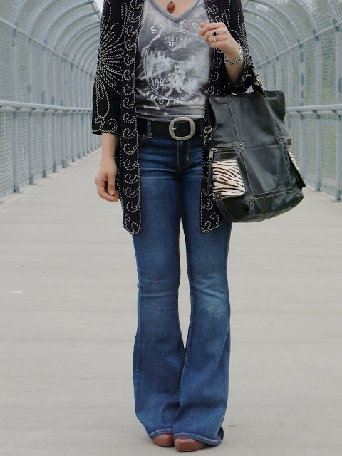 styling flare jeans with a graphic tee, embroidered jacket, and floppy hat