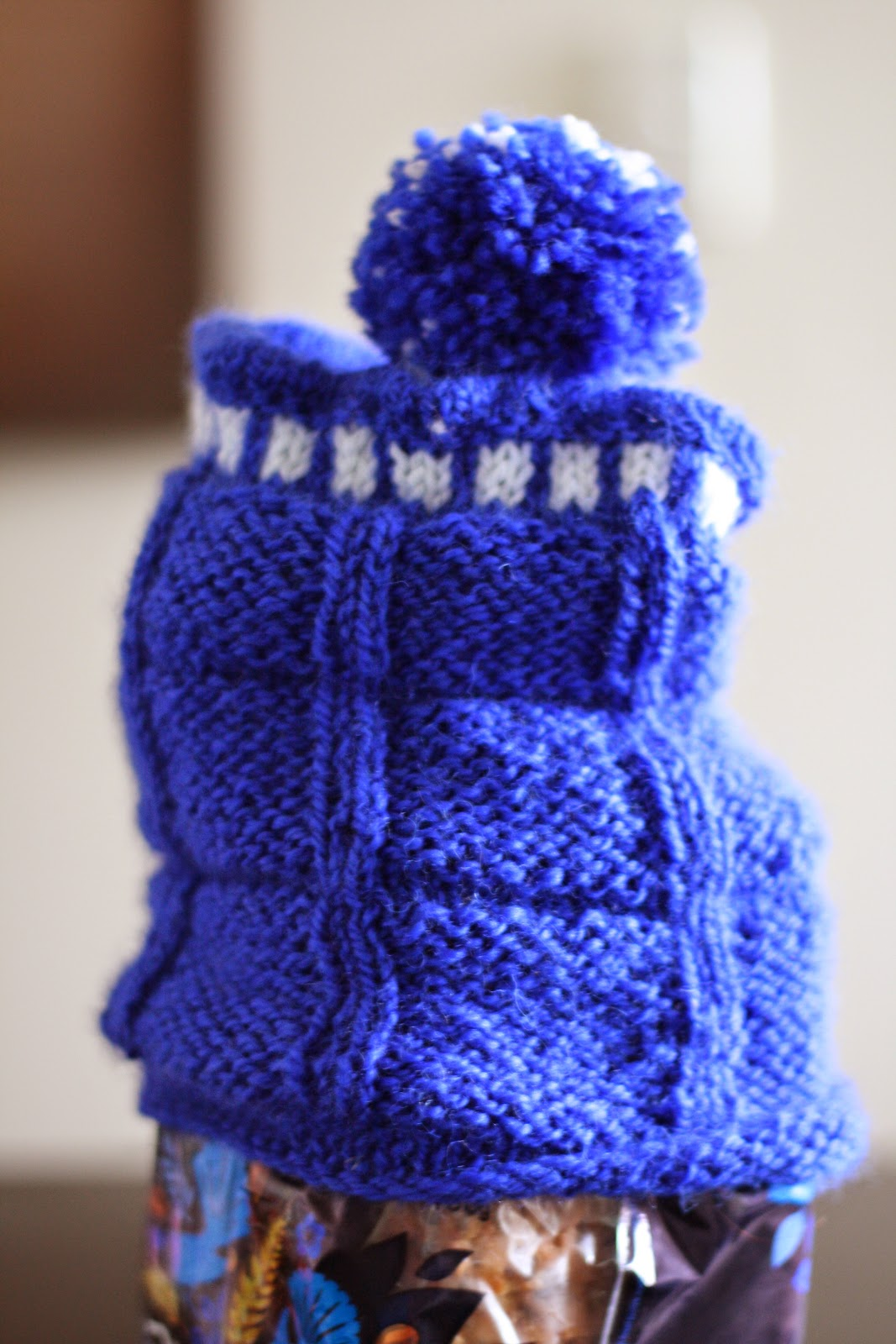 A blue tardis hat with a pom pom sitting on a loaf of bread.