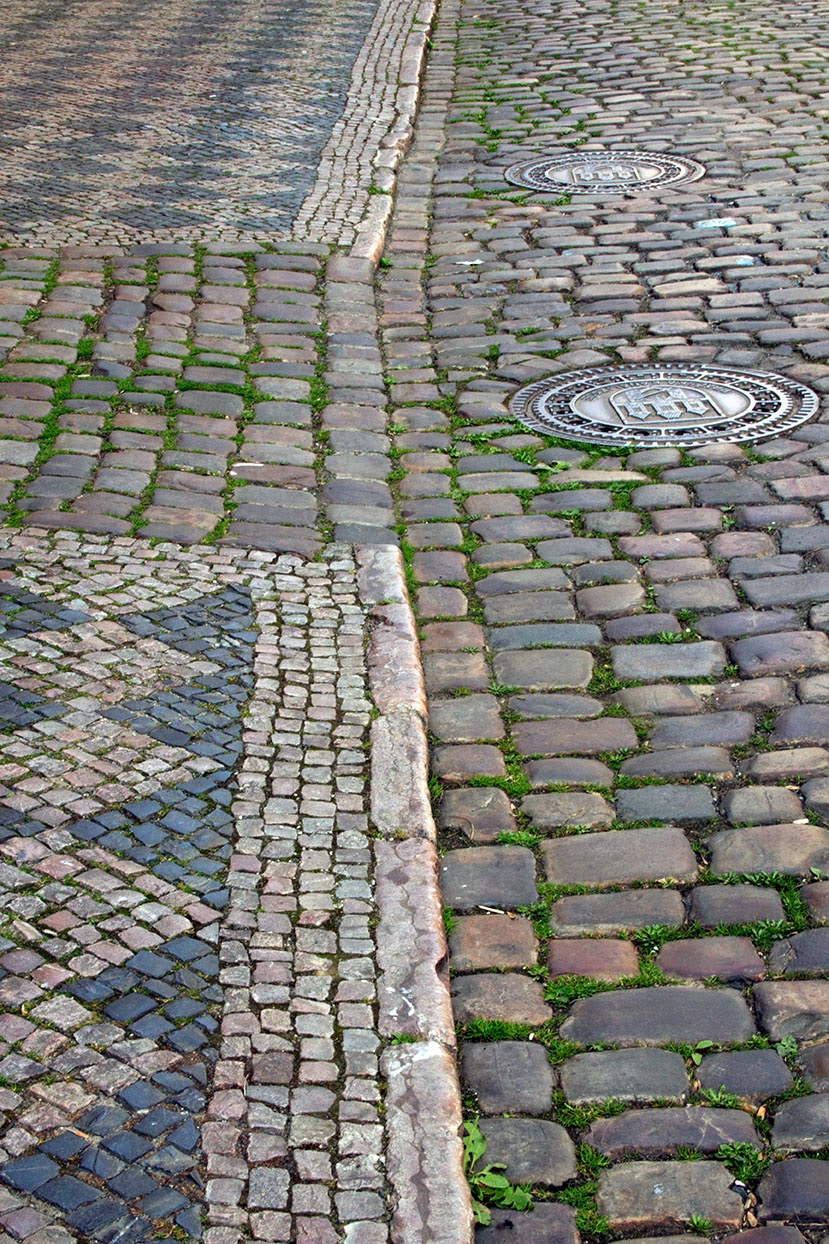 centuries old sidewalk of Prague with manholes