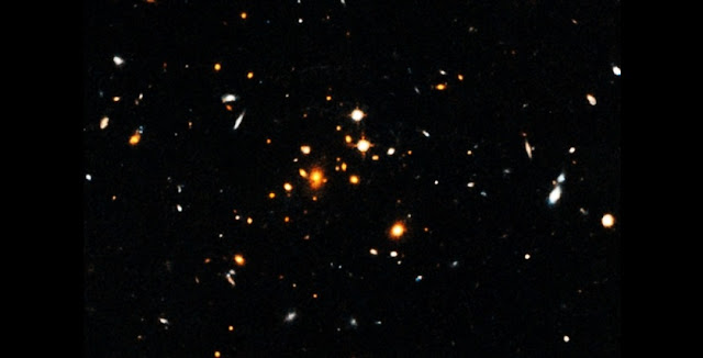 Astronomers have detected a massive, sprawling, churning galaxy cluster that formed only 3.8 billion years after the Big Bang. The cluster, shown here, is the most massive cluster of galaxies yet discovered in the first 4 billion years after the Big Bang.  Image: NASA, European Space Agency, University of Florida, University of Missouri, and University of California