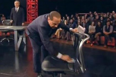 Silvio Berlusconi cleansing the chair where Marco Travaglio sat previously at Servizio Pubblico
