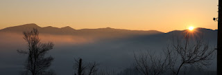 The first rays of the day shine across the valley fog