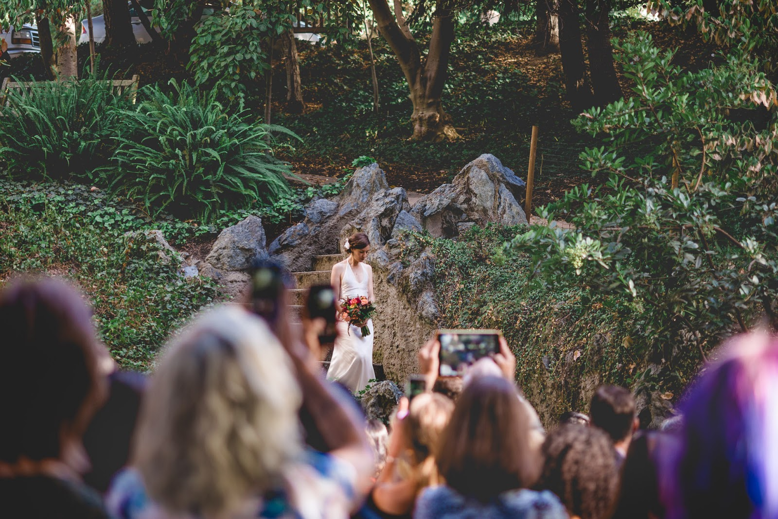 bride walking down the aisle among a sea of cell phones