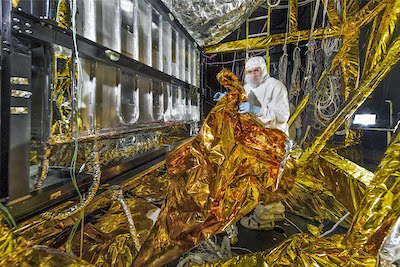 An engineer adjusts thermal insulation on the James Webb Space Telescope's instrument module (ISIM) inside the cryogenic test chamber at NASA's Goddard Space Flight Center. Credit: NASA/Chris Gunn