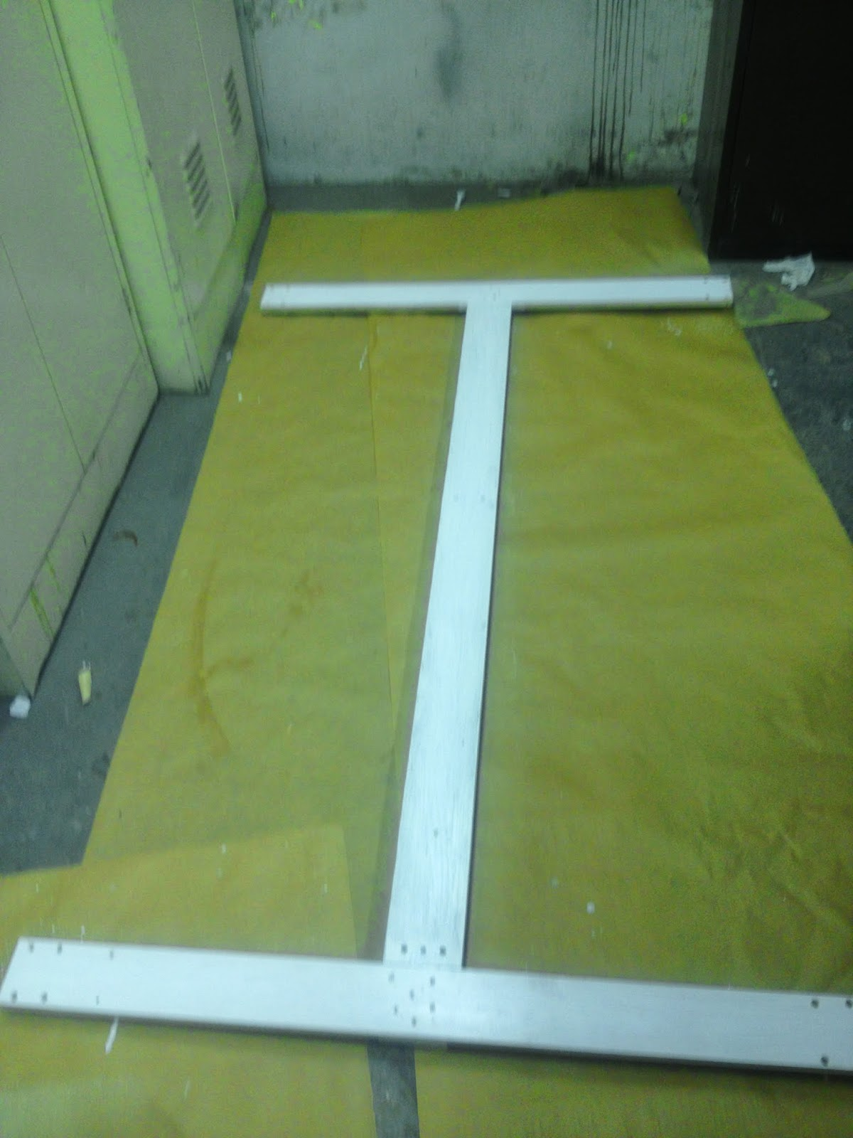 The three dolly pieces are laid out to dry on a plastic after having been painted white.