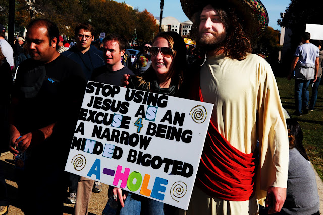 "A guy dressed as Jesus next to a girl with a sign that says, ""Stop Using Jesus As An Excuse For Being A Narrow Minded Bigoted A-Hole""."