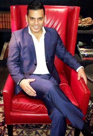 Tito El Bambino con linda sonrisa sentado en un sillón rojo