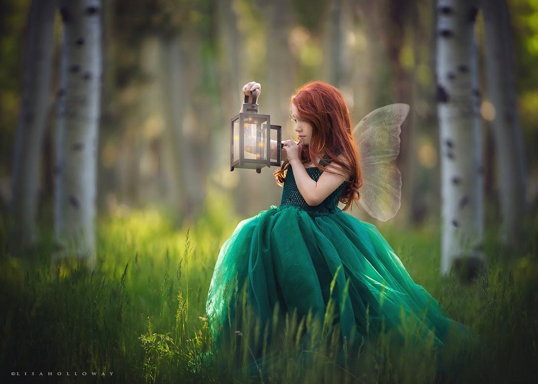 photo de Lisa Holloway représentant une jeune fille en robe verte et petite ailes d'anges tenant une lampe ancienne dans une forêt