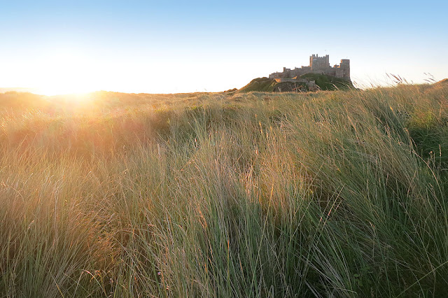 a hazy glow of the rising sun over the sand dunes at Bamburgh Castle