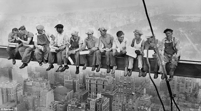 Black and white photo of eleven workers sitting on the steel beam on top of the skyscraper