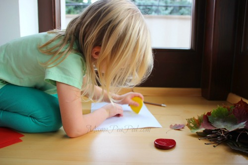 child making leaf rubbings with crayons
