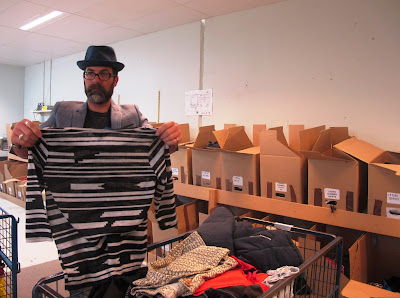 Man holding up an item of clothing in front of a run of labelled cardboard boxes.