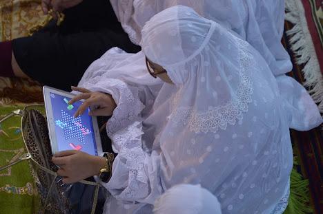 wanita memainkan game pada tabletnya selama khotbah
