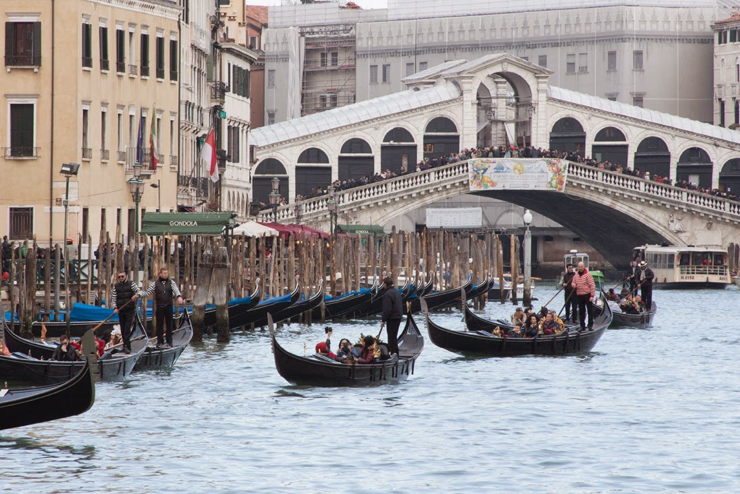 moored and riding gondolas in front of the Rialto bridge