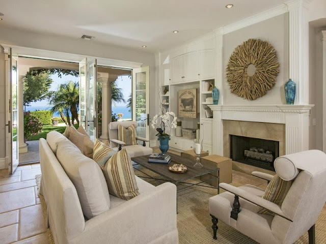 Living room in a Malibu villa with taupe furniture, branch mirror and ocean views