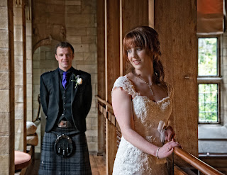 bride in lace gown and soft romantic hairstyle looking to her groom in full kilt outfit