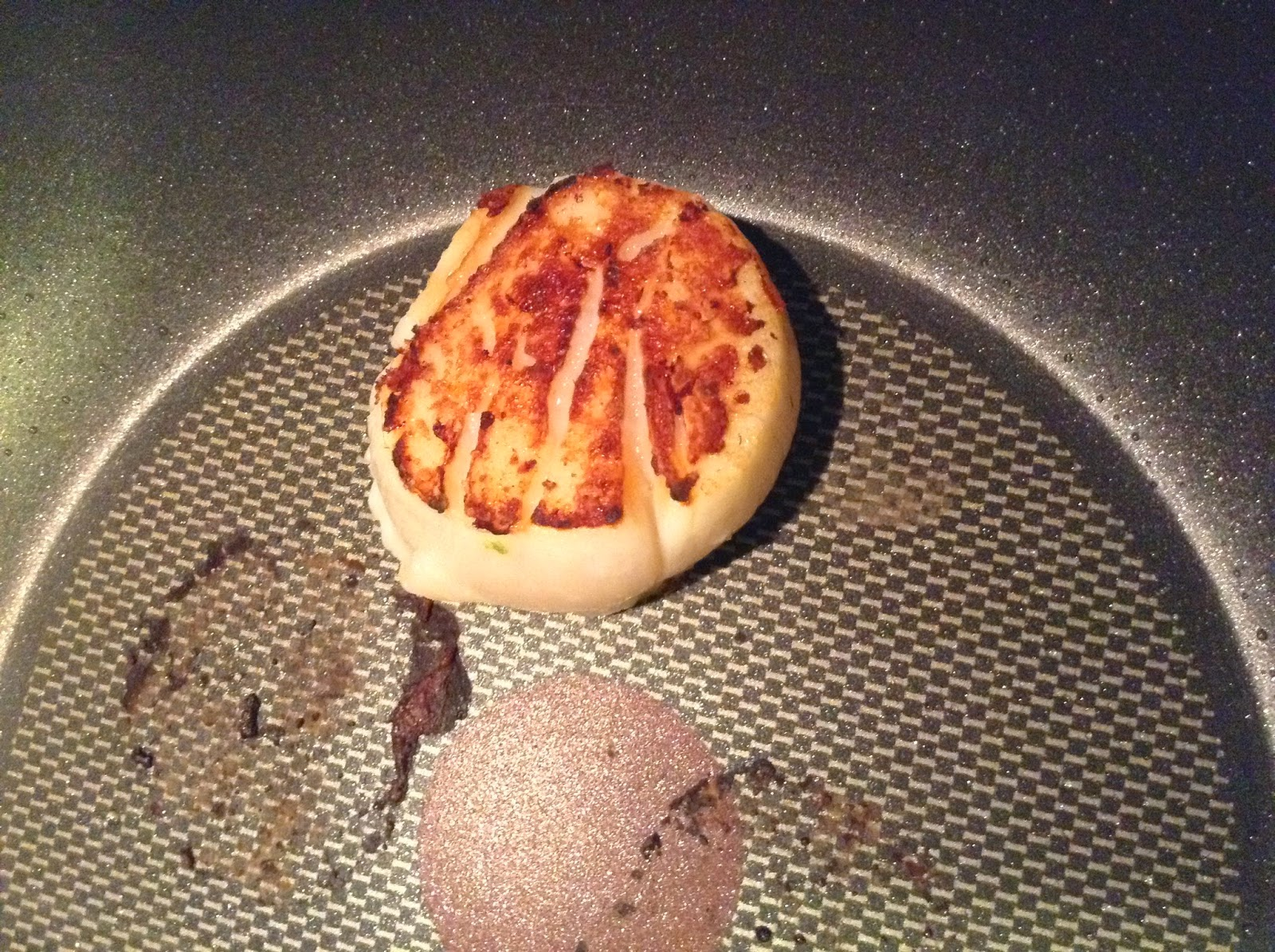 A seared scallop in a pan