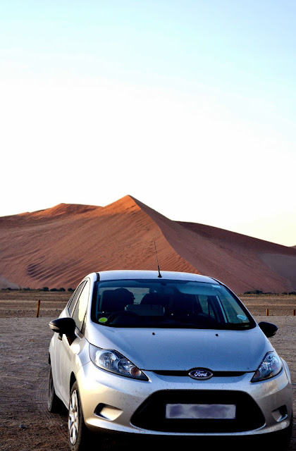 Car in front of sand dune