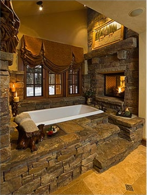 it cant get more rustic then this bathtub base with its rock facade steps built out of stones and roaring fireplace i half expect to see a grizzly bear