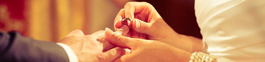 Nakładanie obrączki podczas ceremonii. Kobieta wkłada obrączkę mężczyźnie.