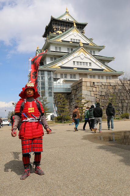 Friendly Japanese cleaner in Samurai costume and he's very proud to take picture in front of Osaka Castle in Osaka, Japan