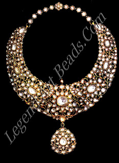 This broad, close fitting gold necklace set with white sapphires combines Indian motifs with foreign elements to produce a lace effect (jail kam).